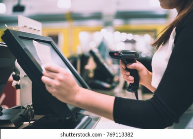 Young woman hands scaning / entering discount / sale on a receipt, touchscreen cash register, market / shop (color toned image)