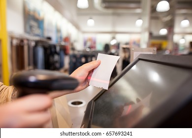 Young woman hands scanning a bill payment for a customer at huge shopping center