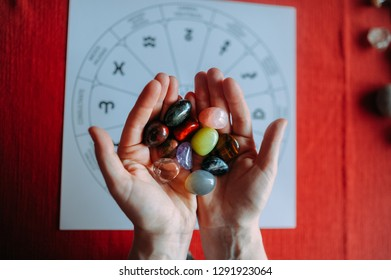 young woman hands showing group of colorful crystal stones during tarot reading with red background