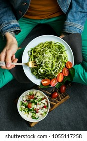 young woman hands twirls zucchini raw vegan pasta with avocado dip sauce around fork, cherry tomatoes and spinach in plate. Top view. Dark background. Vegetarian healthy organic food and diet concept.