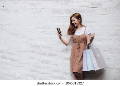 Young woman hands using smartphone to shopping online at the city. Easy E-commerce Website Shop by Smartphone and Laptop. Business and modern lifestyle concept
