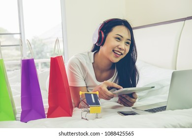 Young woman hands using smartphone to shopping online on the bed. Easy E-commerce Website Shop by Smartphone and Laptop. Business and modern lifestyle concept