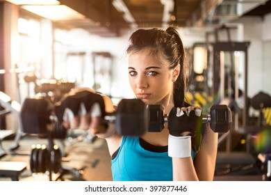 Young woman hang up hand weights.