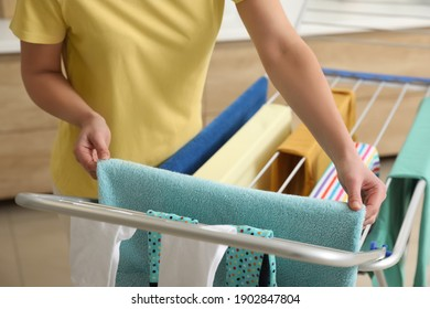 Young woman hanging clean laundry on drying rack in bathroom, closeup