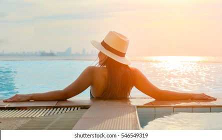 Young woman happy in big hat relaxing on the swimming pool,  travel near the sea and beach in the sunset.  Concept summer
