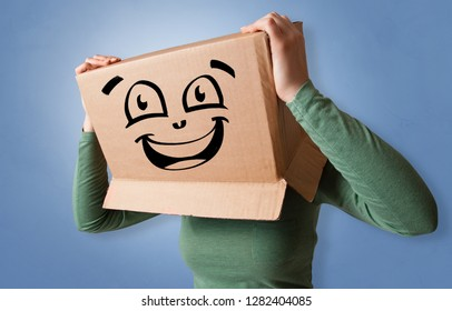 Young woman with happy face illustrated cardboard box on her head