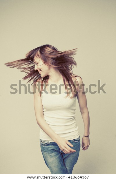 young woman is happy, her face expresses pleasure, she turns her head and her hair scattered on a gray background, vintage color