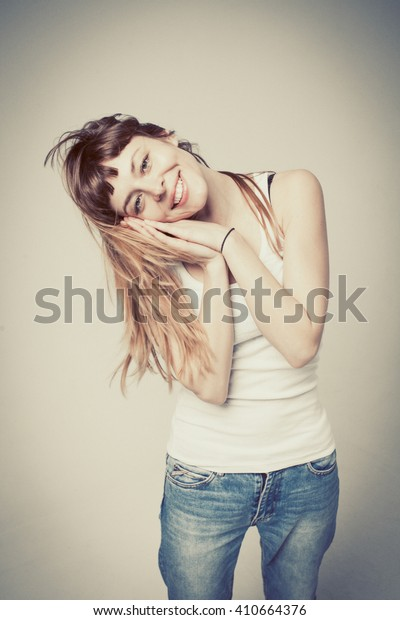 young woman is happy, her face expresses pleasure on a gray background, vintage color