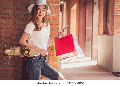 Young woman happy with shopping bags. Easy E-commerce Website Shop by Smartphone, Laptop. Business and modern lifestyle concept