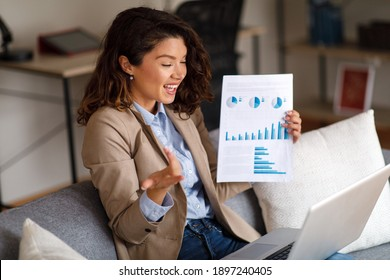 Young woman has a business video call via laptop at home in the sofa and holding papers