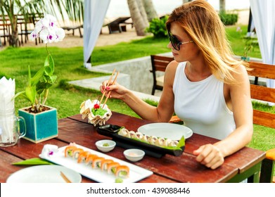 Young woman has a dinner with japanese sushi roll outdoors in lounge zone