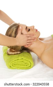 Young woman has face massage in spa.