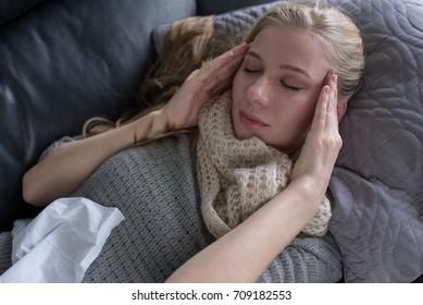 young woman has a headache and holding her head