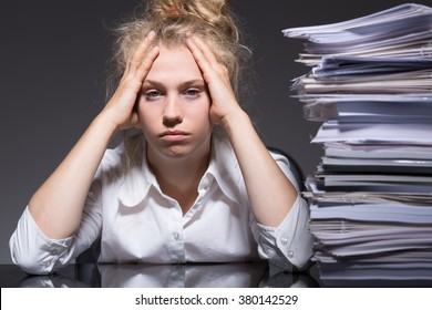 Young woman has lots of paperwork in the office