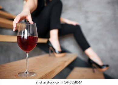 Young woman has problems with alcohol. Cut view of model reaching hand to glass with red wine. Sitting on steps alone. Stylish black female suit.