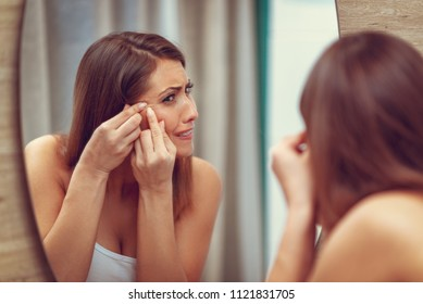 Young woman has problems with skin on the face. She is looking pimple on her cheek in the mirror and frowning.