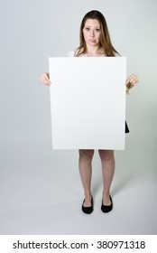 A young woman has a reluctant expression while holding a blank sign, as if not wanting to be the bearer of bad news. She is wearing a black skirt and white blouse. Shot on a seamless white background.