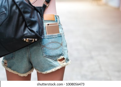 young woman has smart phone in pocket jean