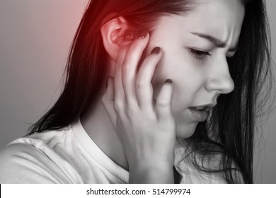 Young woman has a sore ear.  girl suffering from otitis, closeup   over gray background   black and white with red accent