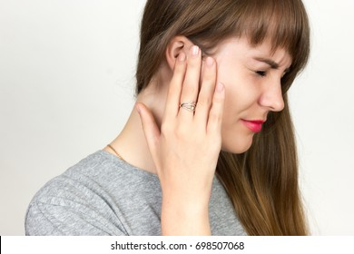 Young woman has a sore ear.  girl suffering from otitis, closeup   over gray background