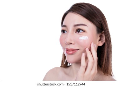 Young woman in hat applying sunscreen on face. Skin care concept.