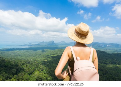 Young woman in hat with backpack enjoying breathtaking view of the landscape from the top of mountain. Travel concept. Back view.