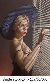 Young woman in a hat by the blinds