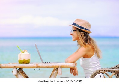 Young woman with hat and coconut using laptop on the beach. Girl Freelancer working