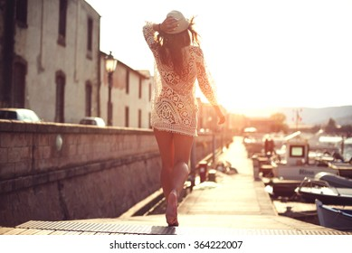 Young woman in hat and cute summer dress standing on the pier with peaceful town scenery, looking at sunset