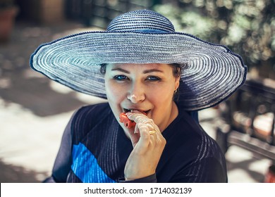 Young woman in a hat eating a watermelon.