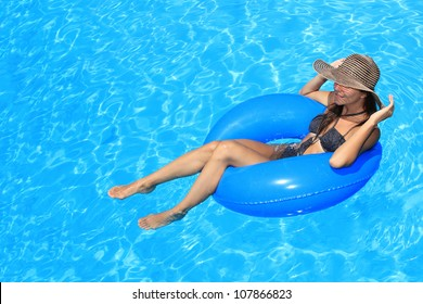 Young woman with hat enjoying a swimming pool
