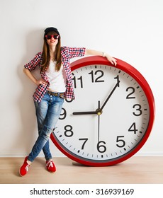young woman with hat and glasses holding a clock. time management concept. nine o`clock