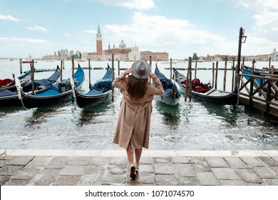 Young woman in a hat on a background of water in Venice
