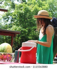 Young woman in a hat at picnic with a cooler and a watermelon