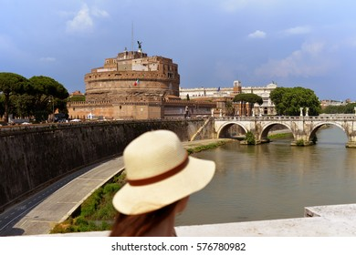 Young woman in hat and Saint Angel Castle over the Tiber river in Rome, Italy