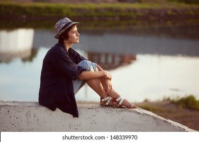 Young woman in a hat sits and rests