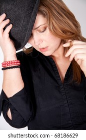 Young woman with hat is smoking a cigar
