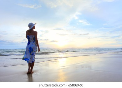 Young woman in hat standing on wet sand and looking to sunset sky