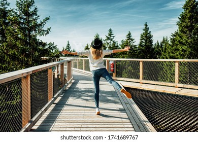 Young woman in  hat stands on wooden bridge with arms raised up among treetops. Concept of freedom, travel, lifestyle. Pohorje Treetop Walk, Rogla. Slovenia, Europe.