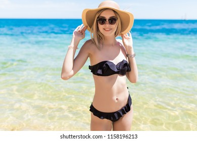 Young woman in hat and sunglasses enjoy fresh water on the beach