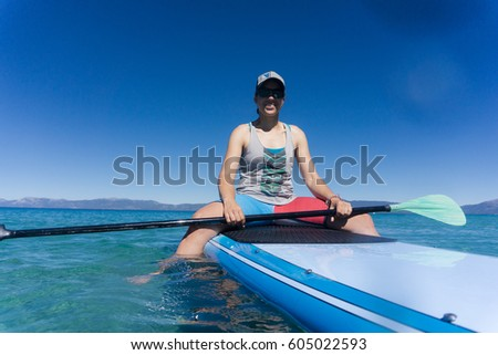 cb72443420 Young woman in hat and sunglasses enjoys watersports on a summer day at  Lake Tahoe