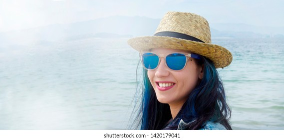 young woman with hat and sunglasses with the sea in the background, concept of travel and vacation