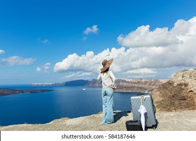 Young woman in hat with umbrella and Luggage looks at the sea