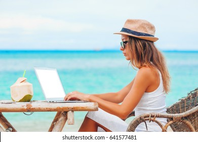 Young woman with hat using laptop with empty white screen on the beach. Girl Freelancer working