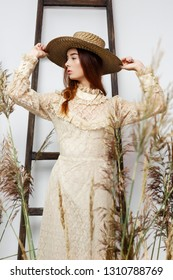 young woman in hat and vintage style dress posing among dry reed