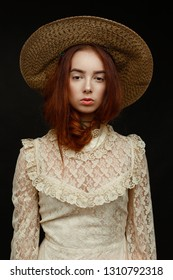 young woman in hat and vintage style dress posing on dark background