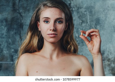 Young woman have allergy and acne on face. She is using special pill to solve this problem.