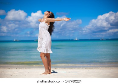 Young woman have fun on beach vacation walking like a bird