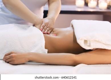 Young woman having abdomen massage. Masseur make massage for stomach