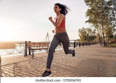 Young woman having active lifestyle exercise outdoors running in the park close-up smiling joyful